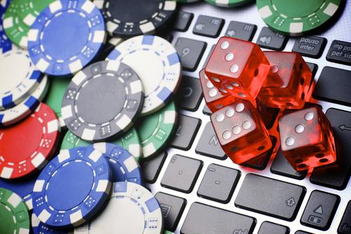 clavier d'ordinateur portable couvert de jetons et de dés de casino