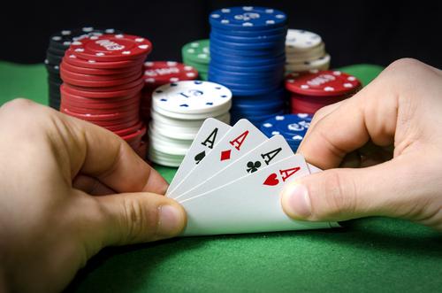 homme tenant un jeu de carte en main