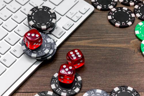 jeton de casino et assortiment de dés sur un ordinateur portable